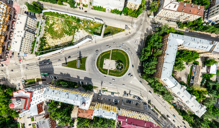 Aerial city view with crossroads and roads, houses, buildings, parks and parking lots. Sunny summer panoramic image 免版税图像