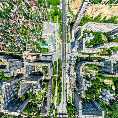 Aerial city view with crossroads and roads, houses, buildings, parks and parking lots. Sunny summer panoramic image Stok Fotoğraf