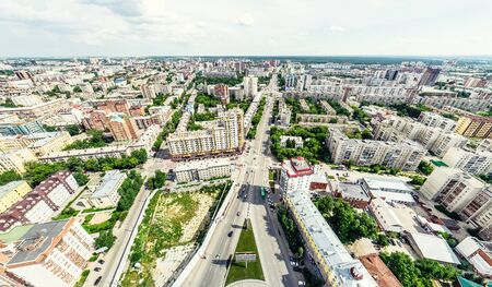 Aerial city view with crossroads and roads, houses, buildings, parks and parking lots. Sunny summer panoramic image Фото со стока