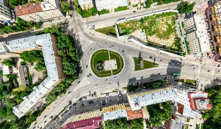 Aerial city view with crossroads and roads, houses, buildings, parks and parking lots, bridges. Helicopter drone shot. Wide Panoramic image. Imagens