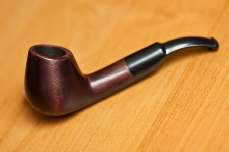 sherlock: Original smoking pipe on wood background. Selective focus. Stock Photo