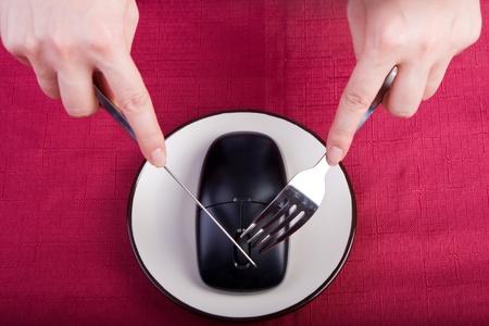 Concetto di mangiare la tecnologia: Hands holding coltello e forchetta un mouse del computer