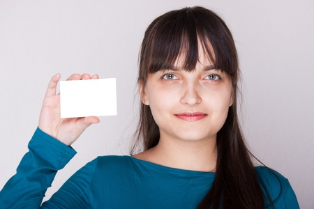 Attractive caucasion girl with business or gift card. Selective focus. Space for text available. Stock Photo