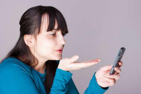 Donna giovane attraente, invio di amore a un cellulare