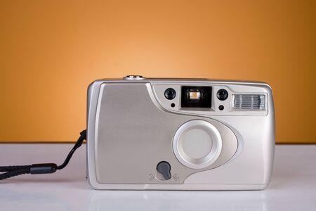 Vecchia macchina fotografica da 35 mm su sfondo arancione