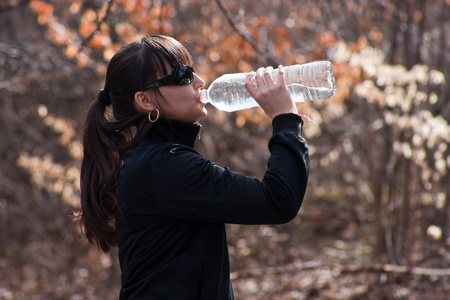 Active girl drinking water in the nature