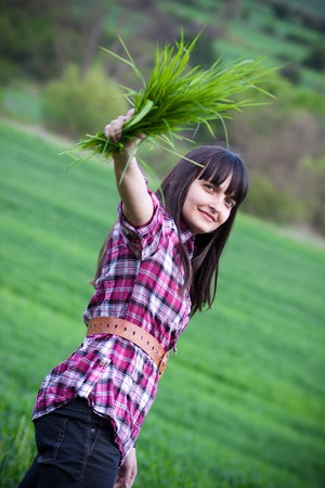Cheerful girl in a green field. Artistic selective focus. Wide aperture shot. Stock Photo