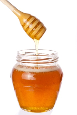 Real honey with stick in a jar isolated on white Stock Photo