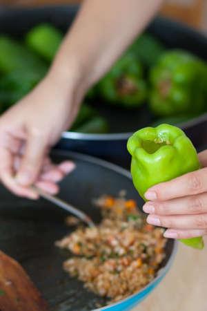 Woman cooking stuffed pepper
