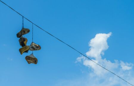 cable tangle: old shoes hanging on the high-voltage wire on blue sky backgroun