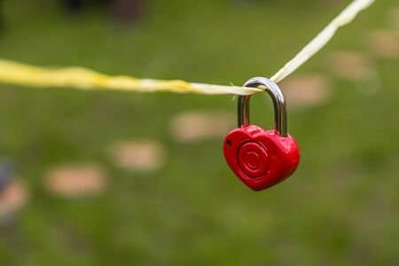 dangling: wedding decor, red lock in the shape of a heart dangling on a rope