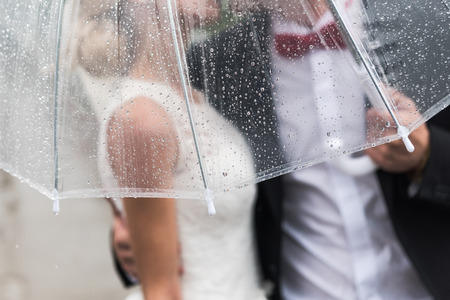 the bride and groom in the rain are covered with a transparent umbrella, rain drops Stockfoto
