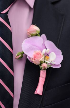buttonhole: a boutonniere of roses and orchids on a blue jacket of the groom
