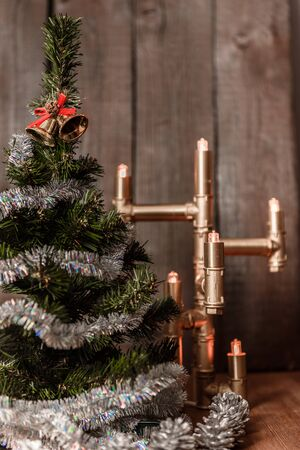 lit lamp: Christmas decorative tree is adorned with rain stands on the table with a lit lamp lights Stock Photo