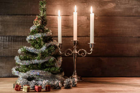 adorned: Christmas decorative tree is adorned with rain stands on the table with lit candles
