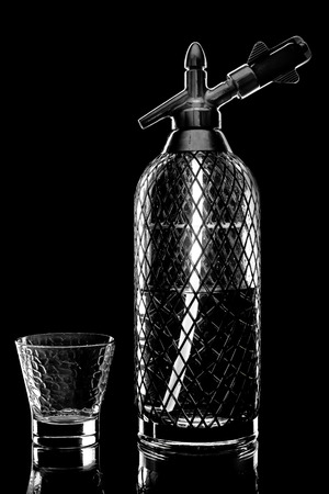 copulation: siphon with soda copulation on the table on a black background with an empty Cup