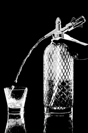 siphon: siphon with soda copulation on the table on a black background with a full glass, jet and drops