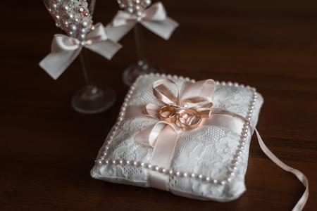 黒いテーブルの上のクッションの上横に金の結婚指輪