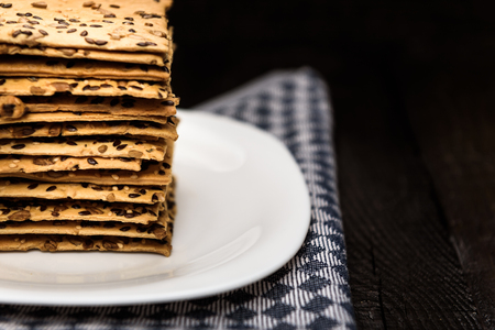 sesame cracker: cookies with sunflower seeds and sesame seeds on a white plate with checkered napkin