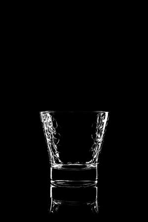 vaso vacio: vidrio transparente para el brandy o el coñac en fondo negro con la reflexión