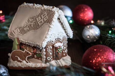 christmas ornamentation: the gingerbread house in the white glaze on the background of the Christmas wreath with Christmas decorations Stock Photo