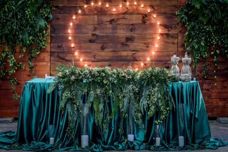 wedding banquet on the background of the heart of the lamps in the forest among the trees on the green track