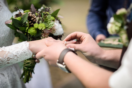 puts: groom puts wedding ring on bride finger Stock Photo