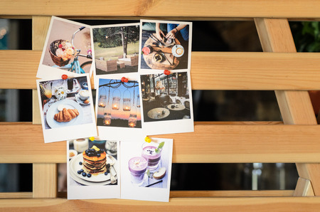 Fotos mit Polaroid über Essen und Reise zu einem hölzernen Gitter gepinnt