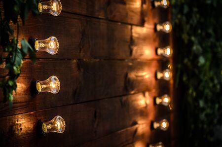 Hochzeitsbankett auf dem Hintergrund des Herzens der Lampen in den Wald zwischen den Bäumen auf der grünen Spur