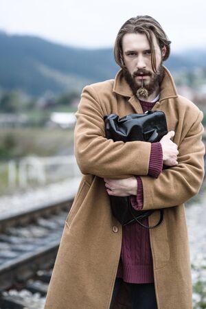 uomini belli: un uomo in un cappotto marrone stand stringendo una valigetta nera su uno sfondo di montagne