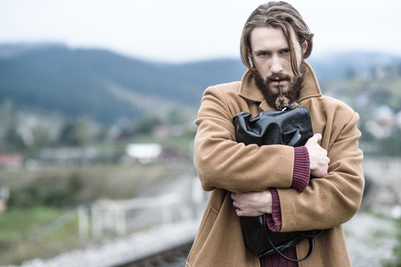 beau jeune homme: a man in a brown coat stands clutching a black briefcase on a background of mountains