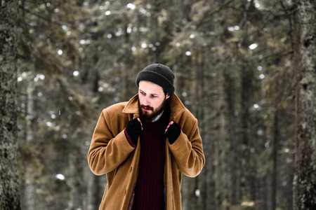 man in the winter forest is cold and in a brown coat and gloves