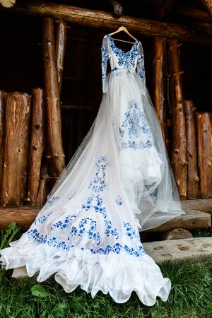 bridesmaid: bridesmaid dress in the style of Gzhel hanging on a wooden beam in the input aperture of the house