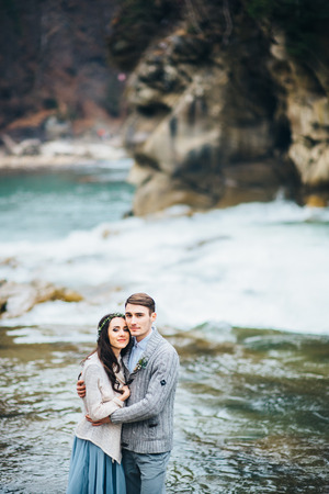man waterfalls: the bride turned to the groom on the background of a mountain river Stock Photo