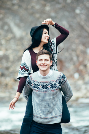 couple nature: guy and girl in warm sweaters by a mountain river, love story