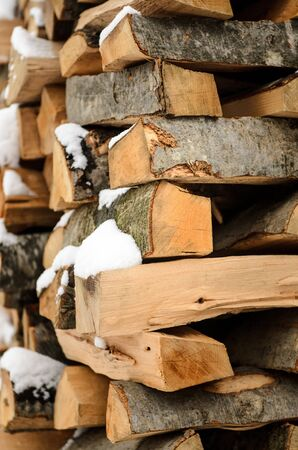 heap of snow: firewood in the snow, chopped singe harvested for fireplace