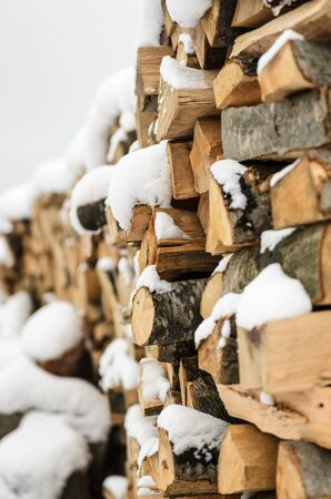 winter wood: firewood in the snow, chopped singe harvested for fireplace