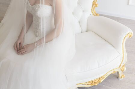 sits on a chair: the bride sits on a vintage white chair