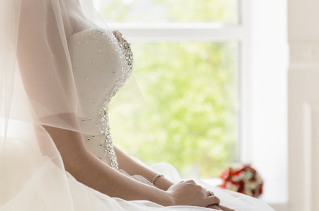 the bride sits on a vintage white chair