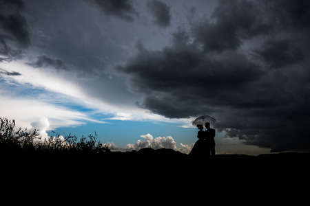 couple under an umbrella in rainy stormy weather Stock Photo