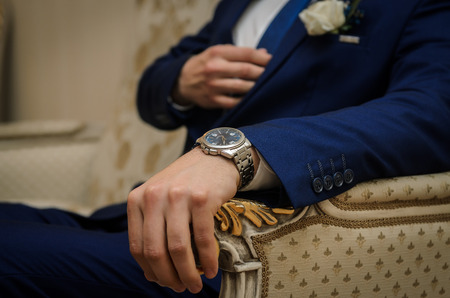 hand cuff: the groom sits in the chair, the hand with the watch in the foreground