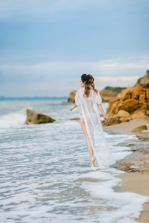 boudoir: bride in her underwear and a dressing gown with a veil walks on the beach Stock Photo