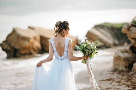 bride with a wedding bouquet on the shore of the black sea in the sunset light