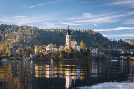 Lake Bled in the Alpine mountains in autumn under blue sky