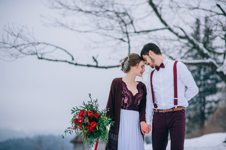 groom in a brown and bride in burgundy in the mountains Carpathians