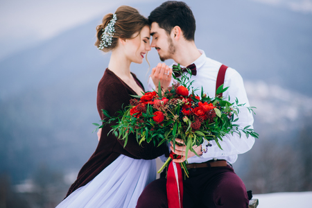 Groom in a brown and bride in burgundy in the mountains Carpathians Stock Photo