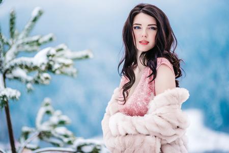 dziewczyna z kasztanowymi włosami, niebieskimi oczami i różową sukienką na tle zimowych gór