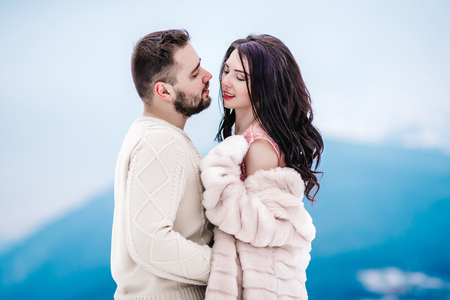 a bride in a fur coat with a fiance among the Carpathian mountains Archivio Fotografico
