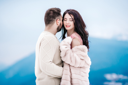A bride in a fur coat with a fiance among the Carpathian mountains Stock Photo