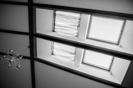 skylights in the roof of the house with a vintage chandelier on the ceiling